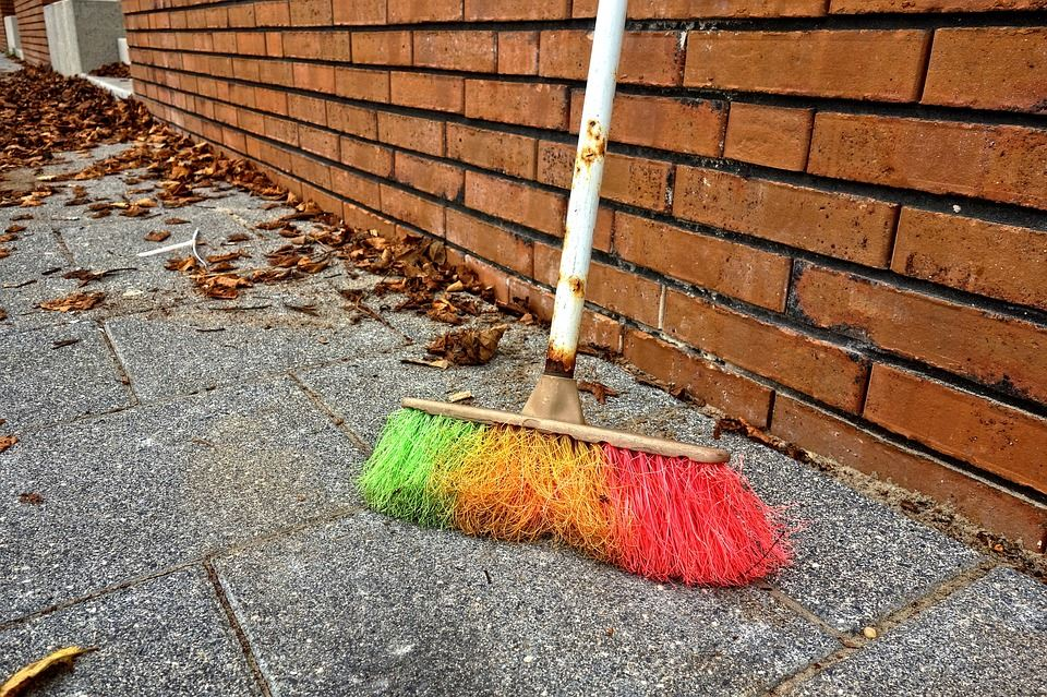 Broom leaning against brick wall
